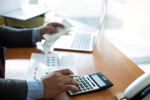 guy using calculator paying bills